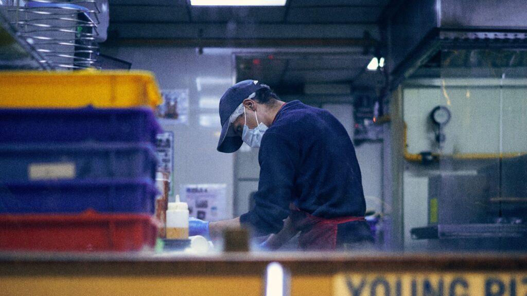 Worker in restaurant wearing face mask